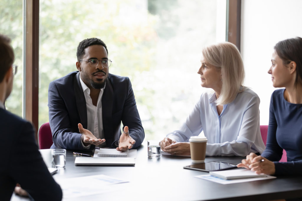 Millenial afro-american businessman talking to partners